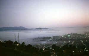 Sitting in my radio car in the Twin Peaks parking lot at sunrise I took this picture of the fog rolling over the Richmond district. September 1973